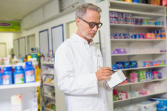 Focused pharmacist writing on box of medicine Royalty Free Stock Images