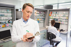 Focused pharmacist writing on clipboard. At the hospital pharmacy Royalty Free Stock Photo