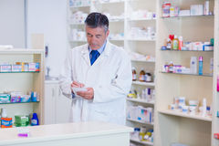 Focused pharmacist writing down notes Stock Image