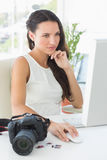 Focused photographer sitting at her desk using computer Royalty Free Stock Photography