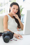 Focused photographer sitting at her desk using computer looking at camera Stock Images