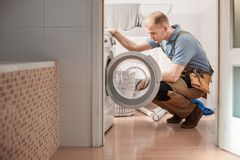 Focused plumber with toolbelt. Thinking how to repair a washing machine in the bathroom Stock Photo