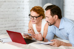 Focused positive couple using laptop at home Royalty Free Stock Photo