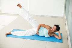Focused pregnant woman exercising at home Stock Photography