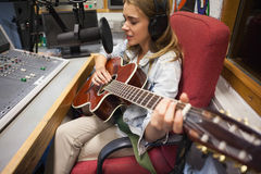 Focused pretty singer recording and playing guitar Stock Photos