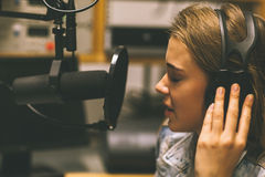 Focused pretty singer recording a song. In studio at college Royalty Free Stock Photos