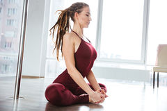 Focused pretty woman doing yoga in studio Royalty Free Stock Photos