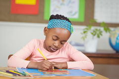 Focused pupil colouring a picture at her desk Stock Photos