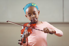 Focused pupil playing violin in a classroom Royalty Free Stock Images