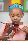 Focused pupil playing violin in a classroom Royalty Free Stock Photos