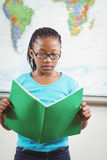 Focused pupil reading book in a classroom Stock Image