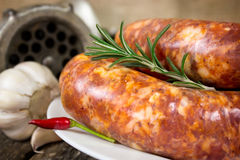 Focused raw sausage on the plate. With meat grinder in the background Royalty Free Stock Image