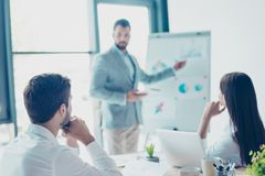 Focused rear view of three colleagues, concentrated on data at t royalty free stock photos