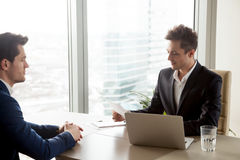 Focused recruiter reviewing resume of male applicant during job Stock Photography
