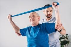 focused rehabilitation therapist assisting senior man