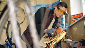 Focused repairmen in protective glasses is working with electric circular saw in studio with wooden walls and spare. Focused repairmen in protective glasses is stock footage