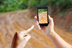 Focused on right hand holding dirt road mobile Stock Image