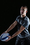 Focused rugby player looking away while holding ball Stock Photos