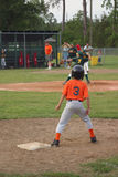 Focused Runner. Little league runner focused on the pitcher as he waits to steal second base Stock Image
