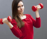 Focused 20s office girl holding dumb bells for toned arms and wellbeing Stock Images