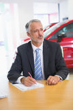 Focused salesman writing on clipboard at his desk Royalty Free Stock Photography