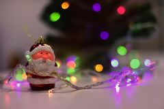 Delicated christmas scene with a santa claus ornament and bokeh colorful lights. Focused santa claus at one side tagled with some christmas lights, and bokeh Stock Photos