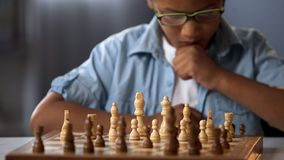 Focused school boy thinking of attacking and capturing opponent chess pieces royalty free stock photo