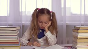 Serious focused school girl at table making homework and writing in a school notebook. Focused school girl stack making homework and writing in a school notebook stock video