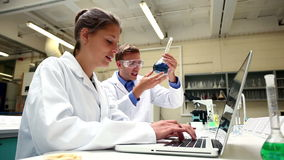 Focused science students examining chemical and using laptop stock footage