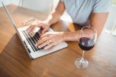 Focused senior man using laptop and drinking wine Stock Photos