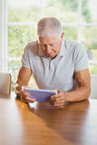 Focused senior man using tablet. At home Royalty Free Stock Image
