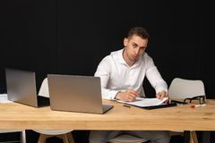 Focused serios businessman thinking of online task stock image