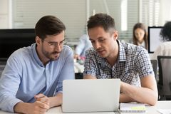 Focused serious male coworkers talking working together on compu royalty free stock images