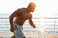 Focused shirtless african man running on pier in the morning Royalty Free Stock Photos