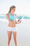 Focused slender blonde in sportswear using tablet Stock Photography