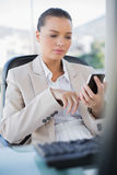 Focused sophisticated businesswoman text messaging. In bright office Stock Photo