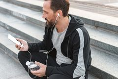 Focused sportsman in earphones. Using mobile phone while sitting on steps with water bottle outdoors royalty free stock photography