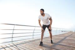 Focused sportsman is ready to start running on pier Stock Photo