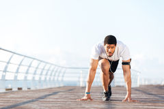 Focused sportsman in running start position on pier. Portrait of focused african american sportsman in running start position on pier Stock Photo