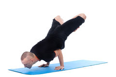 Focused on sporty man posing in complex yoga pose Royalty Free Stock Image