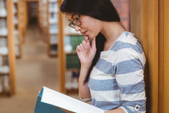 Focused student leaning against bookshelves and reading a book in library Stock Photos