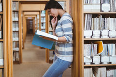 Focused student leaning against bookshelves and reading a book in library Stock Image