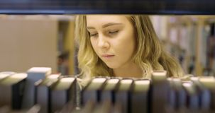 Focused student looking for a book in school library. Woman try to find a book at college or university library. Female student doing research at school stock footage