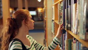 Focused student picking a book in the library. In college stock video footage
