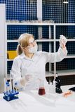 a focused student-science works in a lab with a test tube. Chemistry. Biology. Analyzes. Virus. stock photo