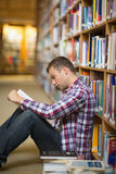 Focused student sitting on library floor reading. In college Royalty Free Stock Photography