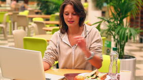 Focused student studying while having lunch in canteen Royalty Free Stock Photo