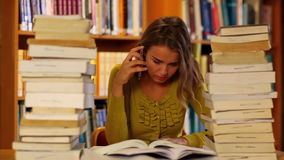 Focused student studying in the library surrounded by books stock video footage