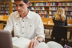 Focused student using his laptop while working. In library Royalty Free Stock Photography