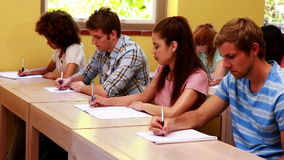 Focused students sitting in a line writing in classroom Stock Images